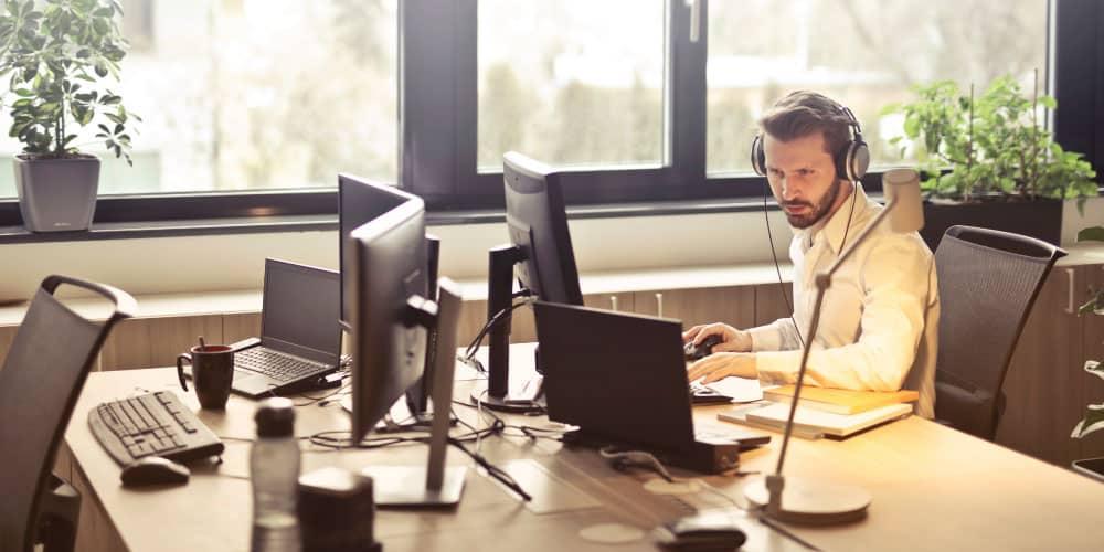 A man with headphone facing computer monitors
