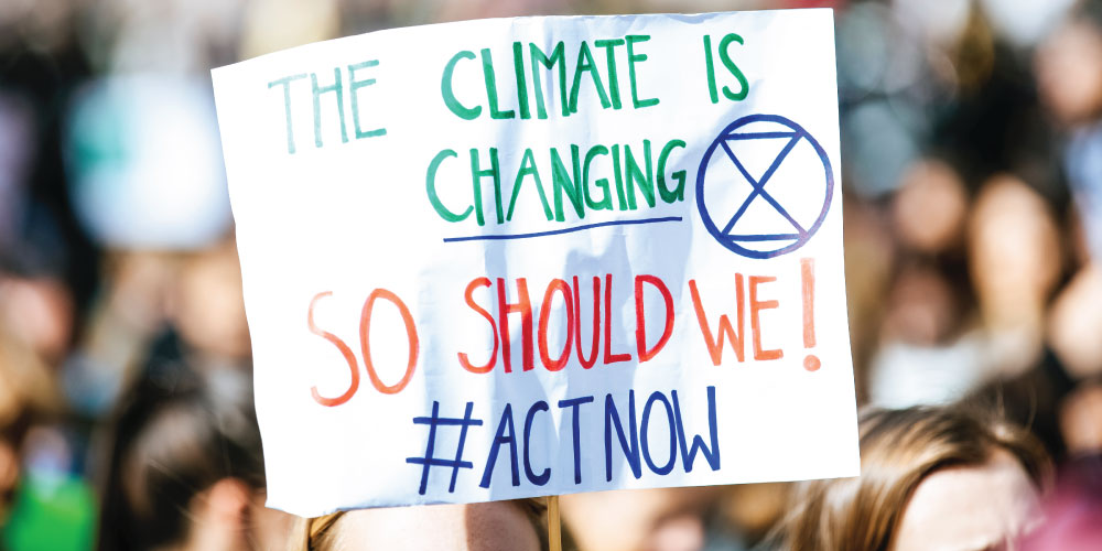 A person holding a sign advocating for climate change reform