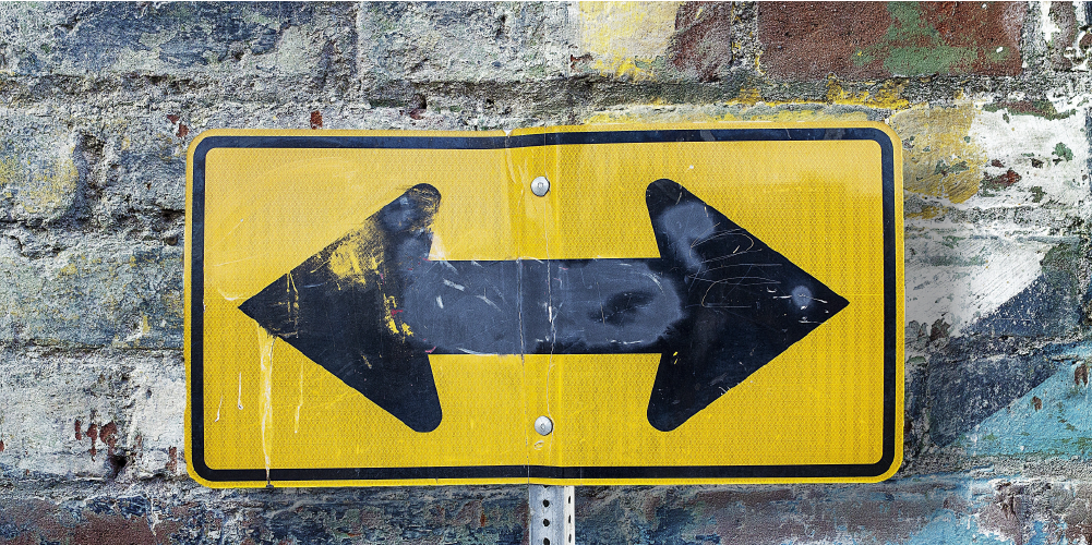 yellow road sign on a brick wall with a black arrow that points opposite directions